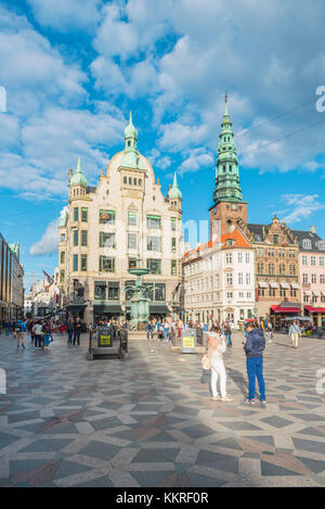Copenhagen, Hovedstaden, Denmark. Tourists and bars in Amager square (Amagertorv) with St. Nicholas church in the - Stock Photo