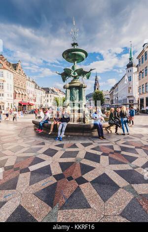 Copenhagen, Denmark. Tourists at the Storkespringvandet, or Stork Fountain in Amager square (Amagertorv). - Stock Photo