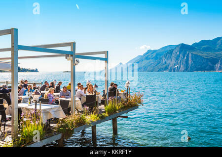 Malcesine, lake Garda, Verona province, Veneto, Italy. Tourists eating out in a restaurant on water. - Stock Photo