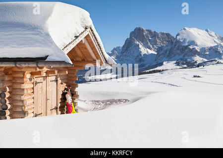 a couple of skiers are relaxing under the sun on the Seiser Alm with the Langkofel Group in the background, Bolzano - Stock Photo