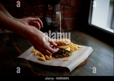 The man takes the Burger.The chef adjusts the ingredients. The concept of fast food - Stock Photo