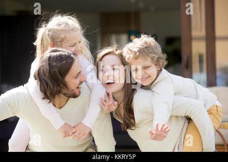 Happy smiling parents piggybacking son and daughter, family leis - Stock Photo