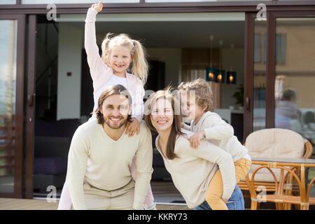 Happy family having fun on house terrace looking at camera - Stock Photo