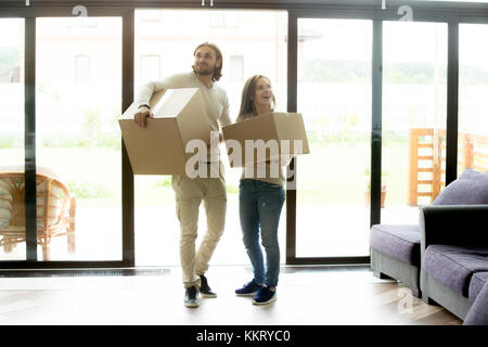 Happy couple holding boxes entering house, moving in new home - Stock Photo
