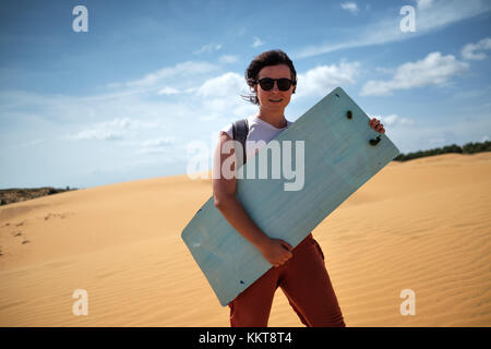 Caucasian girl in sunglasses ready to go sandsurfing. SHe holds surf in her hands and smile. - Stock Photo