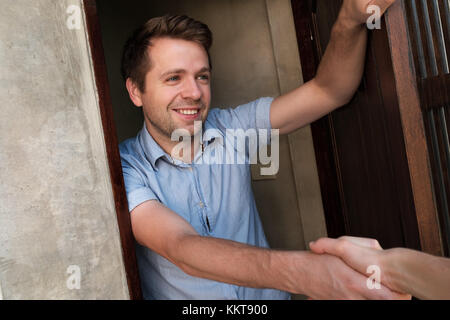 Portrait of young smiling man opening the door to his friend and welcoming him shaking hand - Stock Photo