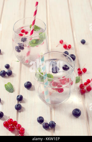 Selective focus on the berry fruit in front glass wth soda water - Stock Photo