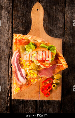Slice of the pizza on the board.Selective focus on the pizza - Stock Photo