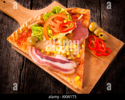Slice of the pizza on the wooden board.Selective focus on the pizza - Stock Photo