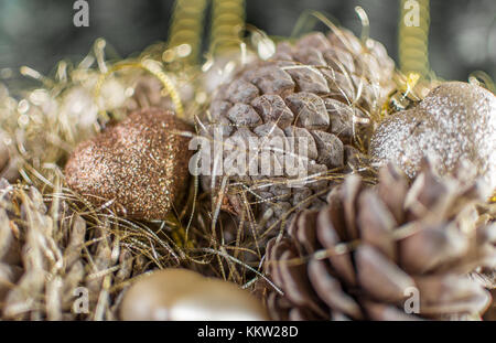 Colorful golden Christmas decorations of a wooden basket with pine cones made with desaturated grainy effect. Extreme - Stock Photo