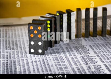 Domino on financial newspaper - Stock Photo
