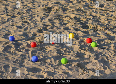 Six game bowls and a small red jack on the sea beach in the summer - Stock Photo