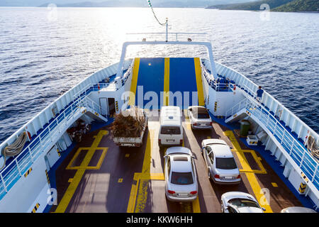 Above view on ferryboat's deck with parked cars until is crossing over calm sea. - Stock Photo
