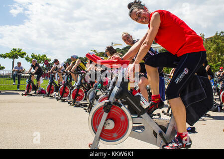 People who are riding on an exercise bike in a public urban park in Imperia. -----Imperia, IM, Italy - May 18, 2014: - Stock Photo