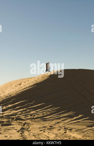 Couple kissing at Imperial Sand Dunes Recreational Area, California, USA. - Stock Photo