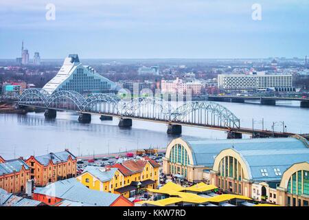 View of Railway Bridge over Daugava River in Riga at sunset in winter - Stock Photo