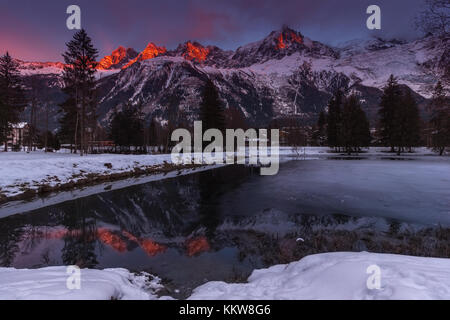 Peaks of Aiguilles of Chamonix at sunset in a cold winter day viewed from Lake das Gaillands - Stock Photo