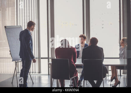 Business plan explained on flipchart by CEO to colleagues - Stock Photo