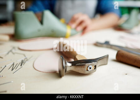 Hammer of shoemaker on workplace with cobbler working on background - Stock Photo