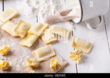 Homemade pasta ravioli and perle on wooden table with vintage mug of flour - Stock Photo