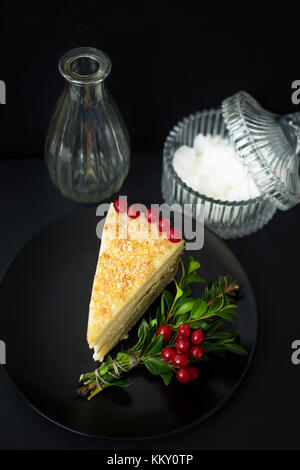 cake decorated Christmas tree branch and red berries on a black background with a vase and saucer - Stock Photo