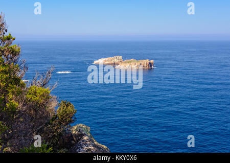 Two small rocky islands surrounded by blue water below the Cape Tourville Lighthouse in the Freycinet National Park - Stock Photo