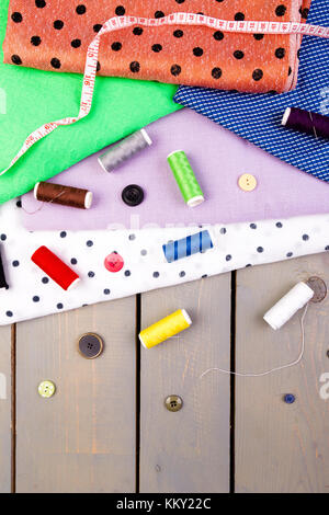 Items for sewing clothes. Sewing buttons, spools of thread and cloth. Top view - Stock Photo