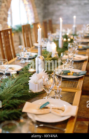 winter, warmness, comfort concept. in the dining hall there is new year feast table decorated with lots of burning - Stock Photo