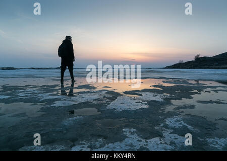 fishing, freedom, nature concept. lonely figure of fish man is standing out on the background of light blue sky - Stock Photo