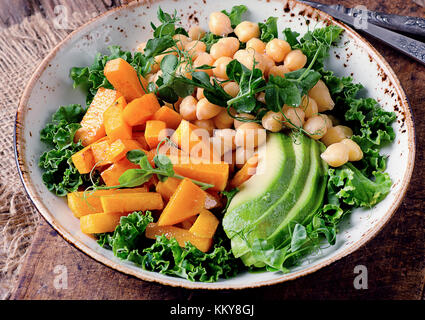 Healthy vegetarian nourishment bowl with chickpea, green pea, pumpkin, avocado, lettuce and pea shoots. Healthy - Stock Photo