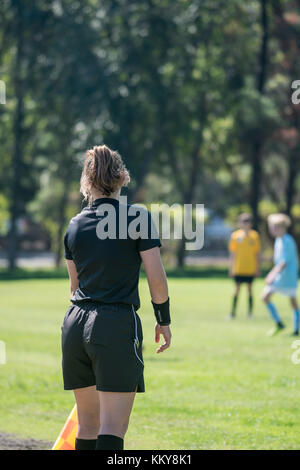 Assistant referee keeping an careful eye on the football players to ensure they are not offside - Stock Photo