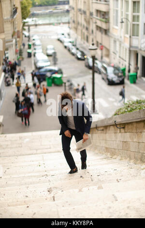 Handsome mulatto boy walking down steps with newspaper. Young man dressed in black suit looking at watch. Concept - Stock Photo