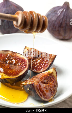 White plate with sliced figs and flowing honey from wooden stick - Stock Photo