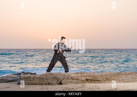 man performs tai chi moves agains sunset at the beach - Stock Photo