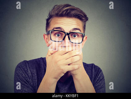 Portrait of a shocked young man covering his mouth with hands - Stock Photo