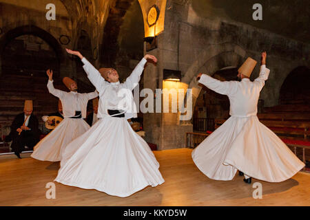 Whirling dervishes performing in an old caravansary in Nevsehir, Turkey. - Stock Photo