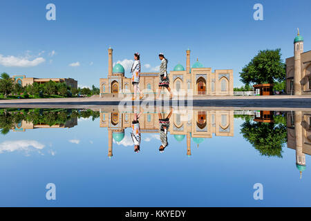 Reflection in puddle of water of the Khast Imam Mosque as girls walk in its courtyard, in Tashkent, Uzbekistan. - Stock Photo