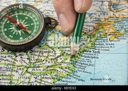 Compass on a map pointing at United States and planning a travel