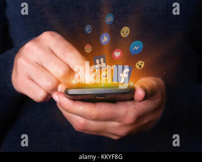 Woman hands holding using smartphone mobile cell phone Facebook social media network app Like messenger friends - Stock Photo