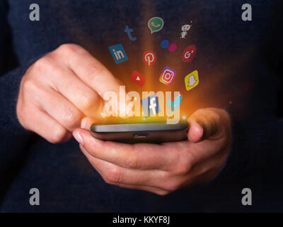 Woman hands holding using smartphone mobile phone checking social media network apps Facebook twitter YouTube Instagram - Stock Photo