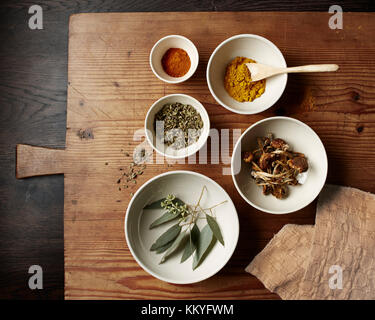 Spices, mushrooms and leaves in varying white bowls on a rustic wooden cutting board with a textured linen napkin - Stock Photo