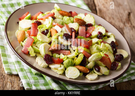 Homemade salad of sliced Brussels sprouts, cranberries, almonds and ham close-up on a plate on a table. horizontal