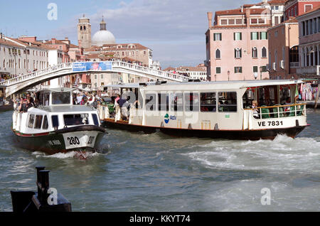 Ponte de Scalzi, across the Grand Canal in Venice, view from the west, with Vaporettos arriving and departing nearby - Stock Photo