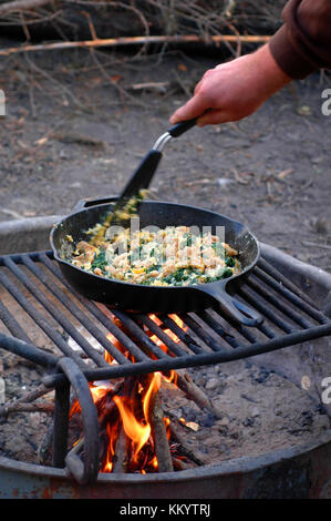 Man cooking an egg scramble with spinach and sausage in a cast iron skillet over a campfire - Stock Photo