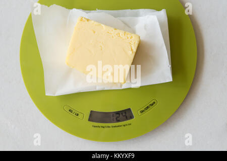 Weighting a stick of butter in preparation for cooking - Stock Photo