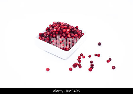 Isolated on white background Lingonberry. Red berries in white plate. - Stock Photo