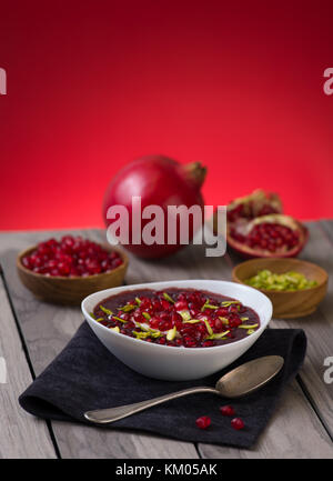 Pomegranate desert with pistachios, Chia Seed, tapioca pudding and Yogurt. healthy eating. red copy space. - Stock Photo