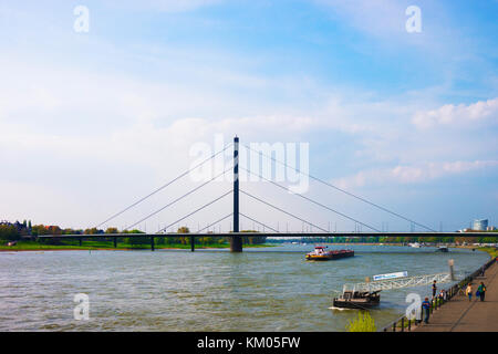 Dusseldorf, Germany - May 3, 2013: Oberkasseler Bridge and Rhine embankment promenade in the Old city center in Dusseldorf, in Germany. Tourists nearb Stock Photo