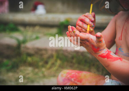 A toddler paints on her hands. - Stock Photo