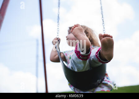 A young girl swings on a swing at a playground in bare feet. - Stock Photo